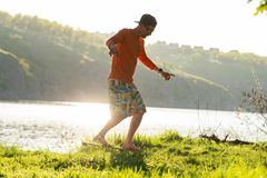 Bearded sporty man is training on the balance board. On a green meadow next to river on sunny evening. Back light Royalty Free Stock Photography