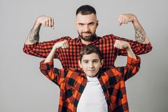 Bearded strong father and his son looking at camera while showing biceps. Handsome bearded strong father and his son looking at camera while showing biceps stock photos