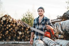 Strong lumberjack wearing plaid shirt hold in hand chainsaw for work on sawmill. Bearded strong lumberjack wearing plaid shirt hold in hand chainsaw for work on stock photo