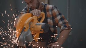 Bearded strong mechanic using electrical angular grinding machine at factory, sparks fly apart. Work in process on metalworking pl. Ant. Horizontal stock video footage
