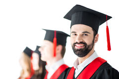 Bearded student in graduation cap with diploma, with friends behind isolated Stock Photos