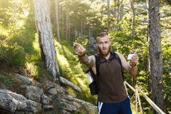 Bearded stylish hiker man using gps navigation for positioning at the mountain trail and thinks where to go. Technology Royalty Free Stock Image