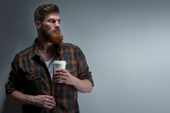 Bearded stylish man with cup of coffee. Dramatic light studio shot of young caucasian bearded stylish man with cup of coffee Handsome hairstyling male portrait royalty free stock photo
