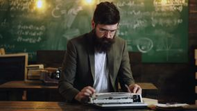 Bearded stylish writer typing on typewriter. Writer working on new book in office. School board background. Literature