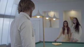 Bearded successful businessman spends leisure playing billiards with two girls. A young man holds a billiard cue while. Bearded successful businessman spends stock video