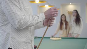 Unrecognized businessman spends leisure playing billiards with two girls. A young man holds a billiard cue while. Bearded successful businessman spends leisure stock video footage