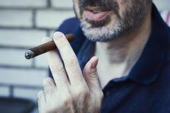 Bearded succusful man chilling and smoking precious cigar. stock image