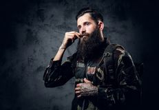 Bearded tattooed male in camouflage jacket. Bearded tattooed male in camouflage jacket over grey background Royalty Free Stock Photo