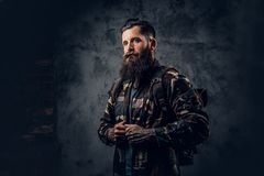 Bearded tattooed male in camouflage jacket. Bearded tattooed male in camouflage jacket over grey background Stock Photography