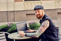 Bearded male using laptop in a summer street cafe. Bearded tattooed male dressed in a waistcoat and tweed cap using laptop in a summer street cafe Stock Photo