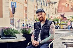Bearded male using laptop in a summer street cafe. Bearded tattooed male dressed in a waistcoat and tweed cap using laptop in a summer street cafe Royalty Free Stock Photography