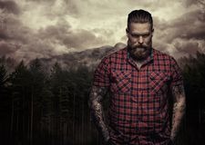Bearded tattooed male in a red shirt. royalty free stock photo