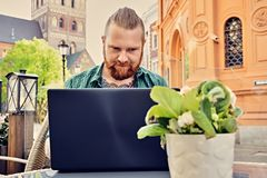 Bearded tattooed male using laptop in an open street cafe. Bearded tattooed male using laptop in an open street cafe in old town Royalty Free Stock Images