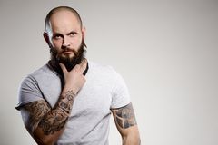 Bearded tattooed man wearing white blank t-shirt royalty free stock photos