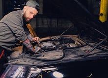 Bearded tattooed mechanics near car in a garage. Portrait of bearded tattooed mechanics near car in a workshop Royalty Free Stock Image
