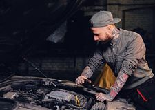 Bearded tattooed mechanics near car in a garage. Portrait of bearded tattooed mechanics near car in a workshop Royalty Free Stock Photography