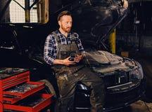 Bearded tattooed mechanics near car in a garage. Portrait of bearded tattooed mechanics near car in a workshop Stock Images