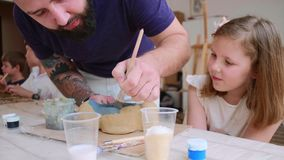 Bearded teacher in shows his pupil girl how to color her handmade toy from clay. Bearded and tattooed teacher is painting in blue color his pupil`s toy using stock footage