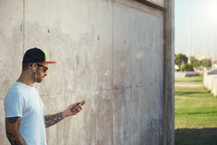 Bearded and tattooed young man holding his smartphone Stock Photo