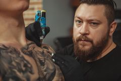 Bearded tattooist making tattoos on body of his client. Cropped close up of a professional tattoo artist looking to the camera fiercely while working royalty free stock photos