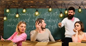 Bearded teacher, lecturer, professor watching students during test, exam, lesson. Cheat on test concept. Students, group. Mates speaking, asking for advice or royalty free stock photos