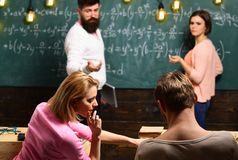 Bearded teacher, lecturer, professor watching students during test, exam, lesson. Students, group mates speaking, asking. For advice or cheating while teacher stock image