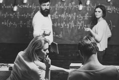 Bearded teacher, lecturer, professor watching students during test, exam, lesson. Students, group mates speaking, asking. For advice or cheating while teacher royalty free stock photo
