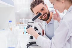Bearded teacher looking at little student working with microscope in lab Stock Photography