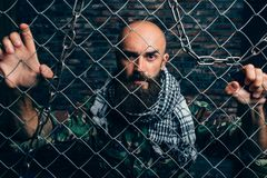 Bearded terrorist in uniform against metal grid. Male mojahed. Terrorism and terror, soldier in khaki camouflage, brick wall on background royalty free stock photos