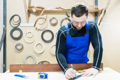 A bearded tired handsome carpenter on a table with a pencil draws a sign on the board. At the workplace there is an. Ordinary master dressed in blue cambenizon Royalty Free Stock Images