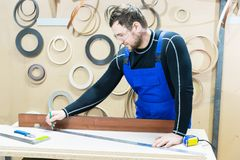 A bearded tired handsome carpenter on a table with a pencil draws a sign on the board. At the workplace there is an. Ordinary master dressed in blue cambenizon Stock Photos