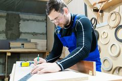 A bearded tired handsome carpenter on a table with a pencil draws a sign on the board. At the workplace there is an. Ordinary master dressed in blue cambenizon Royalty Free Stock Image