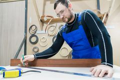 A bearded tired handsome carpenter on a table with a pencil draws a sign on the board. At the workplace there is an. Ordinary master dressed in blue cambenizon Stock Photography