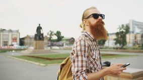Bearded tourist man lost in city and using smartphone online map to find right directions. Bearded tourist man lost in city looking around street and using Royalty Free Stock Photos