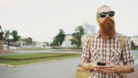 Bearded tourist man lost in city and using smartphone online map to find right directions. Bearded tourist man lost in city looking around street and using Royalty Free Stock Image