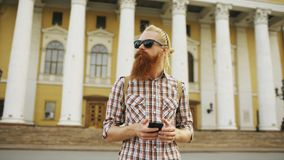 Bearded tourist man lost in city and using smartphone online map to find right directions. Bearded tourist man lost in city looking around street and using Stock Photos