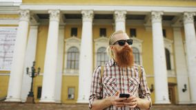 Bearded tourist man lost in city and using smartphone online map to find right directions. Bearded tourist man lost in city looking around street and using Royalty Free Stock Images