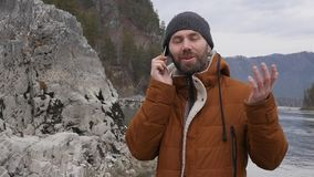 Bearded tourist is having video conference with friends on a mobile phone on the bank of a mountain river. slow motion. Bearded tourist photographs himself on a stock video