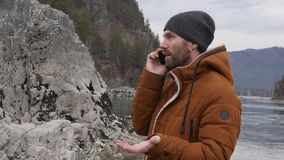 Bearded tourist is having video conference with friends on a mobile phone on the bank of a mountain river. slow motion. Bearded tourist photographs himself on a stock footage