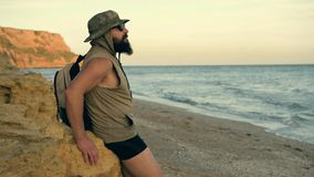 Bearded traveler looking to the beach sky, enjoying sunset at the sea - summer and travel concept. stock video