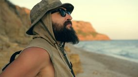 Bearded traveler looking to the beach sky, enjoying sunset at the sea - summer and travel concept. stock footage