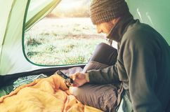 Bearded traveler Man uses his mobile phone sitting in tent stock image