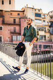Bearded traveller leaning on parapet and looking away Royalty Free Stock Photo