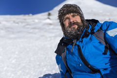 Bearded trekker resting while climbing in winter Royalty Free Stock Photography
