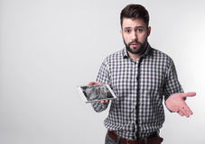 Bearded upset man holds a out-of-use tablet or smartphone. Isolated on a light background Stock Photo