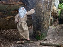 Visionary in the cave shows a finger into the future. Bearded visionary in the cave shows a finger into the future.The old hermit in a cave has an idea royalty free stock photos