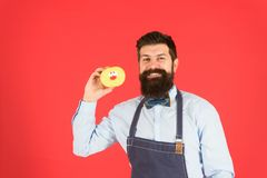 Bearded well groomed man in apron selling donuts. Donut food. Baked goods. Sweets and cakes. Junk food. Hipster bearded royalty free stock image