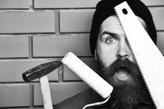 Bearded worker holding various building tools with surprised face. Bearded worker man, long beard, brutal caucasian hipster with moustache holding various royalty free stock photography