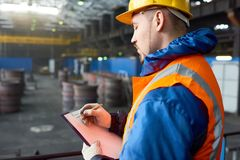 Bearded Worker Taking Inventory. Profile view of concentrated young worker wearing hardhat and reflective vest taking necessary notes while carrying out Royalty Free Stock Images