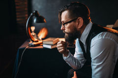 Bearded writer in glasses smoking a pipe. Thoughtful bearded writer in glasses smoking a pipe and look at the window. Retro typewriter, feather, crystal decanter Stock Image